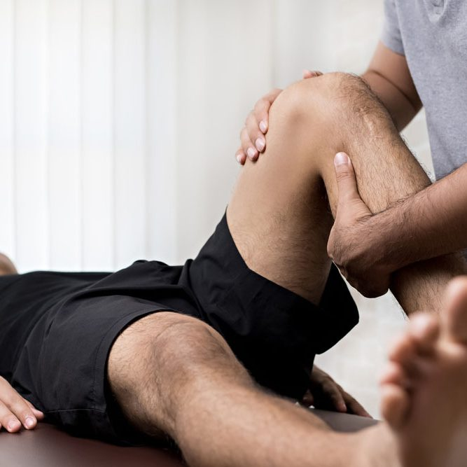 Man having his knee adjusted by Chiropractor - Chiropractic Exercises Pensacola